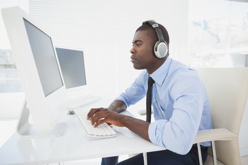 Focused businessman working at his desk listening to music