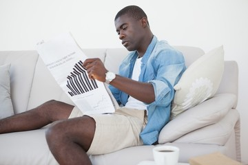 Casual man sitting on sofa reading the paper