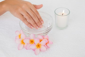 Hand in bowl along flowers and candle