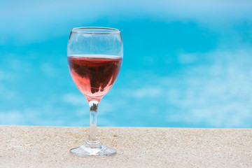 Glass of wine in the pool