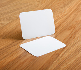 blank business cards with rounded corners on a wooden backgroun