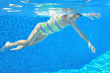 Happy active underwater child swims in pool, girl swimming