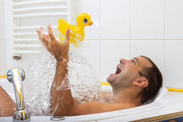man playing in the bath with duck