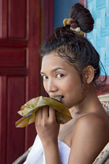 Young woman eat sticky rice steamed in banana leaf Lao style