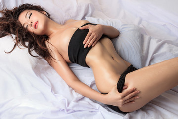 young beautiful fashion female model posing on bed