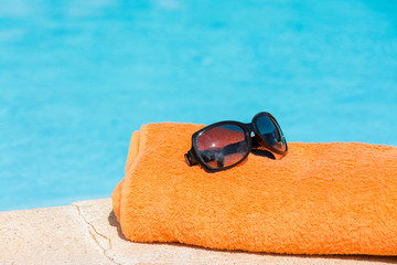 Towel, sunglasses and smartphones in the pool