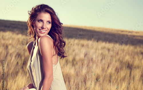 canvas print picture young beautiful woman on golden cereal field in summer