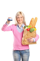 Woman holding bag with groceries and a blank card