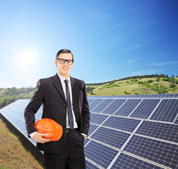 Young engineer standing in front of solar panels