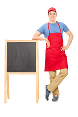 Young vendor standing by a blackboard