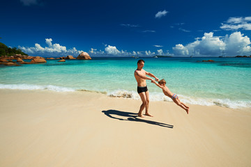 Father and two year old boy playing on beach