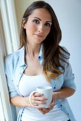 Beautiful woman drinking coffee in the morning near the window.