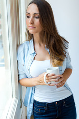 Beautiful woman drinking coffee in the morning near the window.