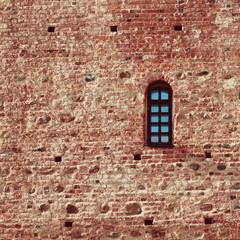 small arched window in a red brick