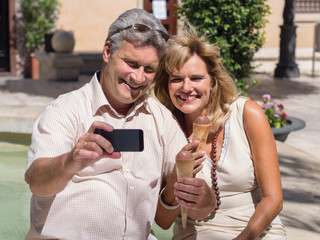 Middleaged mature couple posing for a selfie eating ice cream