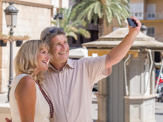 Cheerful mature couple taking selfie picture in holidays