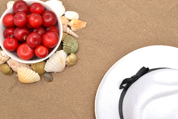 Red plums, shells and white hat on sand