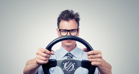 Funny man in glasses with a steering wheel, car drive concept