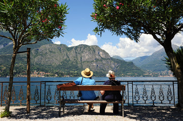 Senior tourists sitting admiring a mountain lake