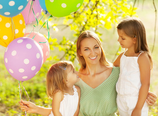 Happy woman and her little daughters in the park with ballons