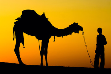 Silhouette man and camel at sunset in desert, Jaisalmer, India