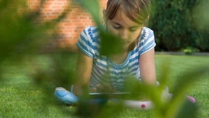 Little girl playing with tablet pc lying on the grass.dolly shot