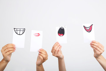 Hands holding up different smileys on grey background