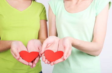 Girls holding red hearts