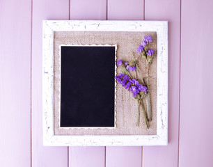 Wooden frame with dried flowers and old blank photo