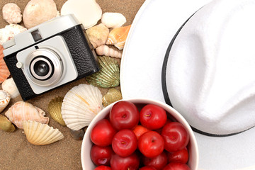 Red plums, old camera, shells and white hat on sand
