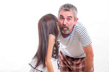 Girl whispering in dad's ear