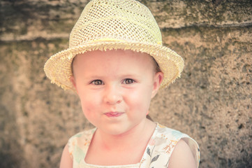 Laughing gorgeous and beautiful little girl in a straw hat