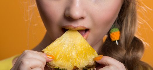 Portrait of a young woman eating pineapple
