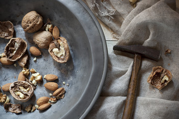 craked walnuts and whole almonds with hammer on vintage plate