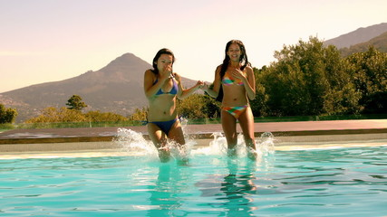 Cute friends jumping into swimming pool together