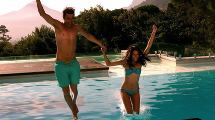 Happy couple jumping in swimming pool together