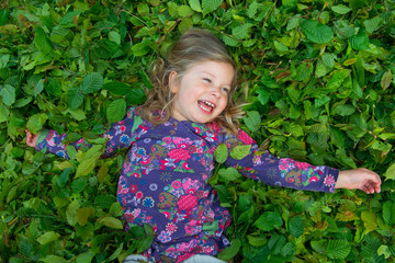 happy girl is lying in green leaves