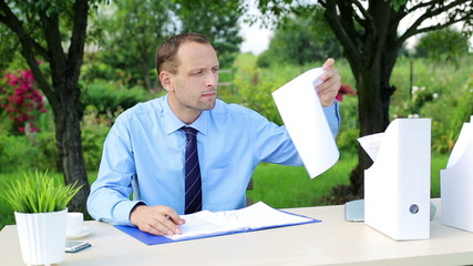 Young businessman working with documents by desk in the garden