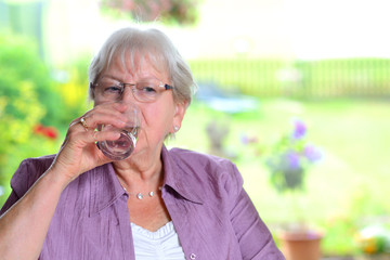 female senior is drinking water