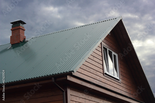 Green metal roof and brick chimney under cloudy sky