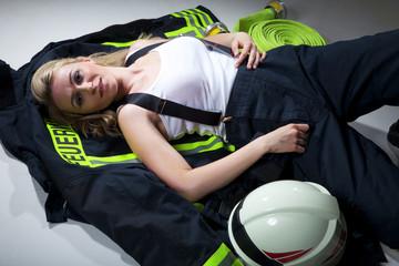 Sexy Feuerwehr Frau liegt am Boden