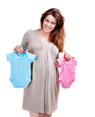 Happy pregnant woman holding two bodysuits for a baby