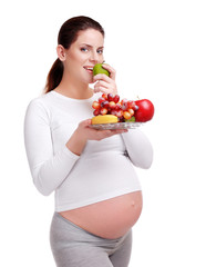 Happy pregnant woman with natural food studio shot