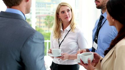 Business people standing at conference drinking coffee