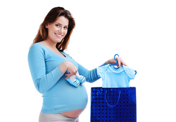 Happy pregnant woman with a paper bag and baby bodysuit