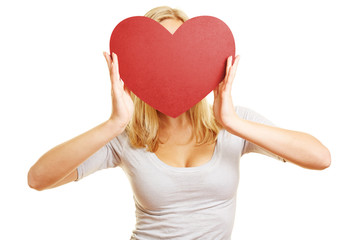 Frau hält rotes Herz vor Gesicht