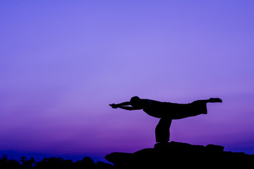 Silhouette of a man in Yoga posting