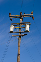 Wood pole with high voltage power lines on blue sky