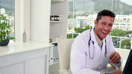 Handsome doctor working at his desk smiling at camera