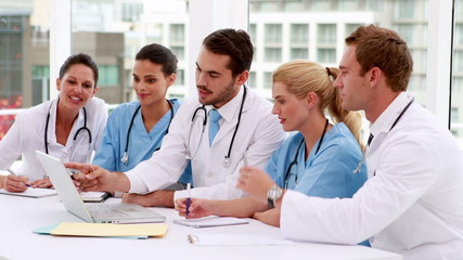 Medical team looking at laptop during meeting